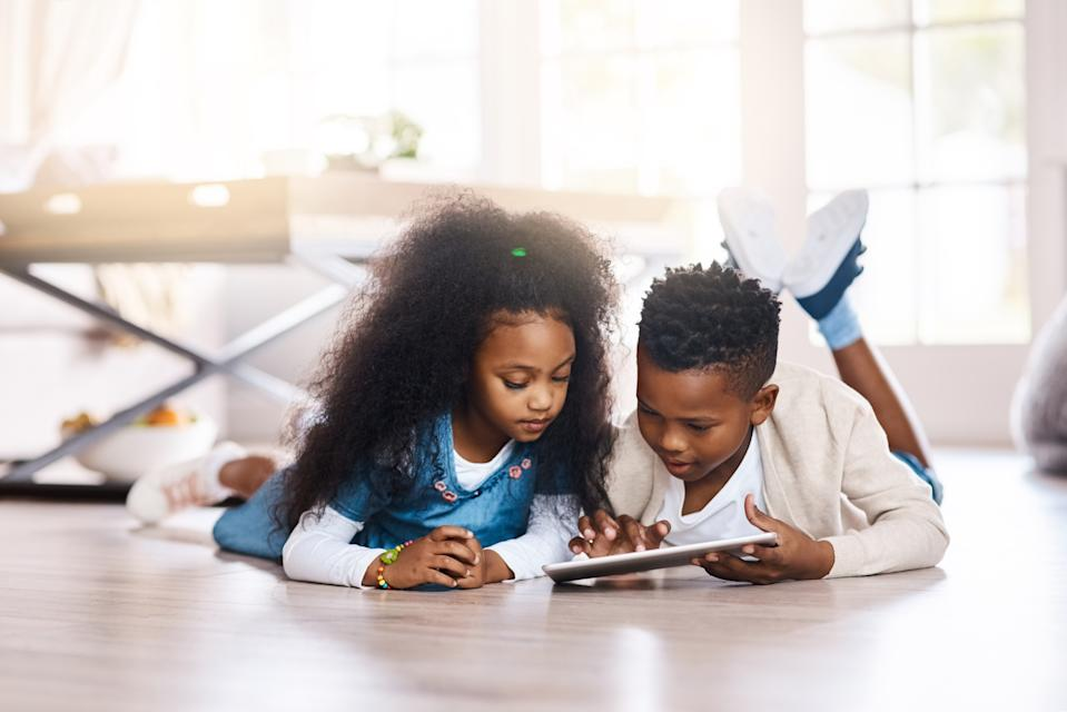 Siblings using a digital tablet together at home. Educational apps can provide a fun activity for kids to help supplement their learning. (Photo: Getty Images)