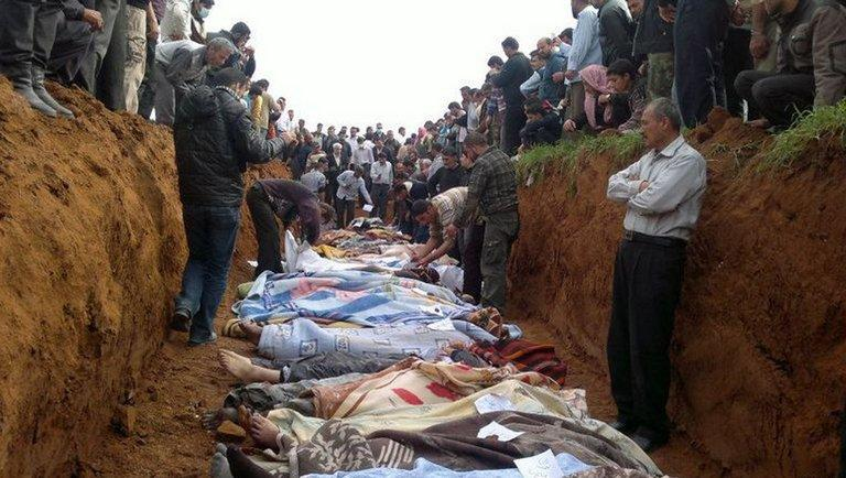 Syrian residents stand around a mass grave in the town of Taftnaz, on April 5, 2012