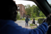 Pastor Marsha Hawkins-Hourd, a community leader in St. Louis, drives past a man standing on a sidewalk in a neighborhood known to locals as a gathering spot for drug use on Tuesday, May 18, 2021. Hawkins-Hourd describes the vacant buildings in the neighborhood as a symbol of addiction and a community thrown away. (AP Photo/Brynn Anderson)