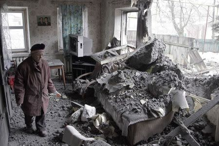 A woman surveys damage done to a house, which according to locals was recently damaged by shelling, in the suburbs of Donetsk January 30, 2015. REUTERS/Alexander Ermochenko