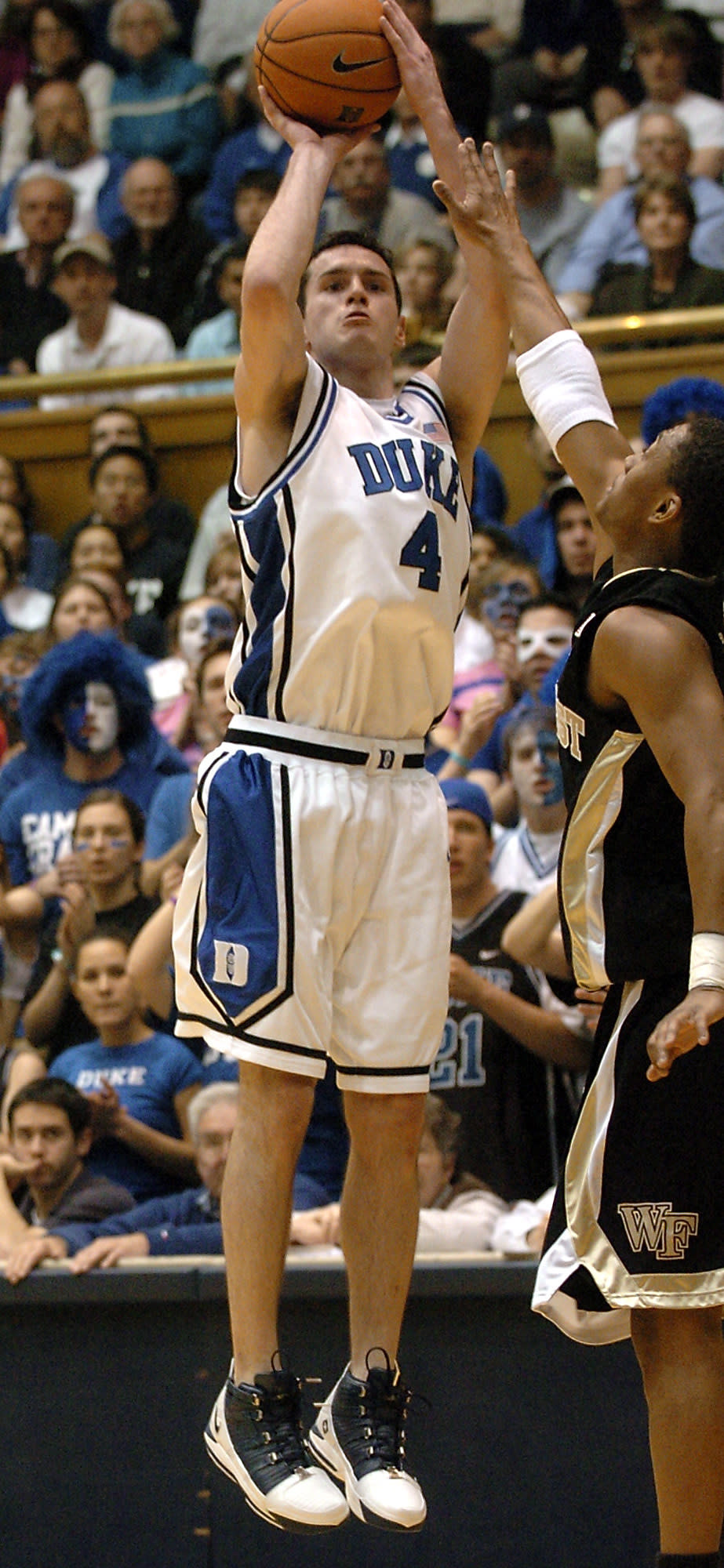 FILE - Duke's J.J. Redick (4) breaks the NCAA record for career high three-pointers made with 414 as he shoots over Wake Forest's Justin Gray, right, in the first half of a college basketball game in Durham, N.C., in this Tuesday, Feb. 14, 2006, file photo. Redick announced his retirement from basketball Tuesday, Sept. 21, 2021, ending a 15-season NBA career that came after he was the AP's college player of the year at Duke in 2006. (AP Photo/Sara D. Davis, File)