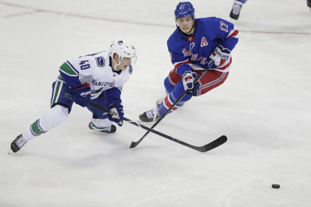 Vancouver Canucks' Elias Pettersson (40) fights for control of the puck with New York Rangers' Jesper Fast (17) during the third period of an NHL hockey game Monday, Nov. 12, 2018, in New York. The Rangers won 2-1. (AP Photo/Frank Franklin II)