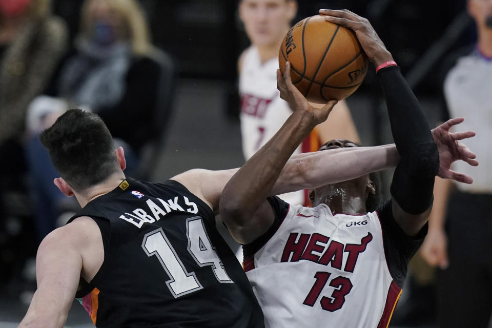 Miami Heat center Bam Adebayo (13) is fouled by San Antonio Spurs forward Drew Eubanks (14) as he drives to the basket during the second half of an NBA basketball game in San Antonio, Wednesday, April 21, 2021. (AP Photo/Eric Gay)