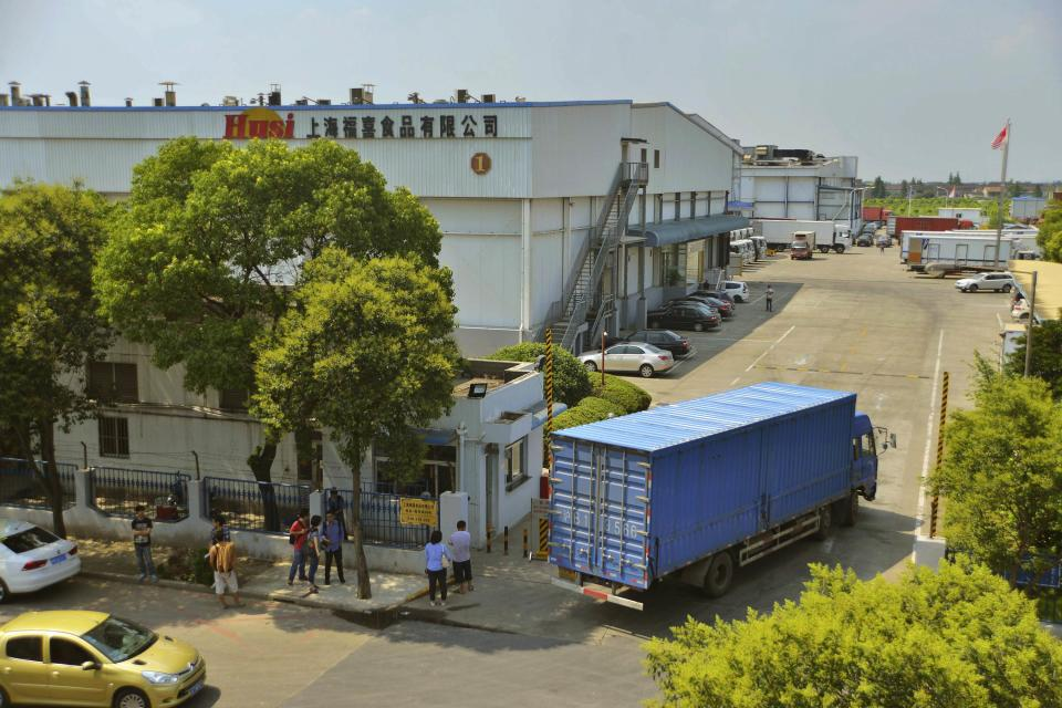 A truck drives past a building of the seized Shanghai Husi Food Co Ltd factory July 21, 2014. The latest food scandal in China is spreading fast, dragging in U.S. coffee chain Starbucks, Burger King Worldwide Inc and others, as well as McDonald's products as far away as Japan. McDonald's Corp and KFC's parent Yum Brands Inc apologised to Chinese customers on Monday after it emerged that Shanghai Husi Food Co Ltd, a unit of U.S.-based OSI Group LLC, had supplied expired meat to the two chains. Picture taken July 21, 2014. REUTERS/Stringer (CHINA - Tags: BUSINESS FOOD) CHINA OUT. NO COMMERCIAL OR EDITORIAL SALES IN CHINA