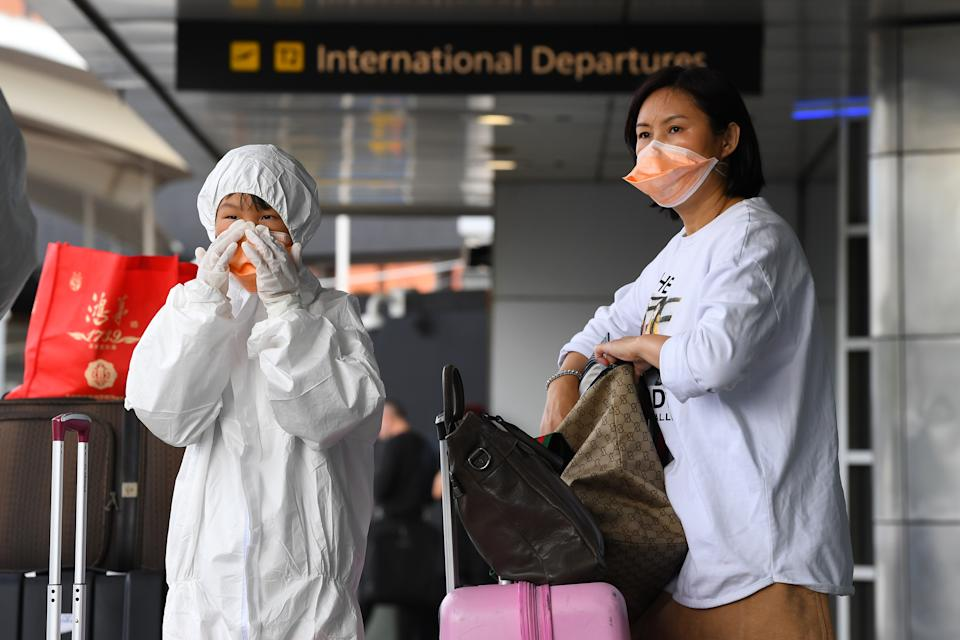 People are seen dressing in personal protective equipment outside the international departures terminal at Tullamarine Airport, Melbourne. Source: AAP