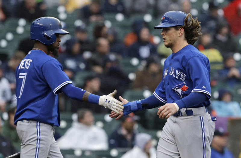 Toronto Blue Jays' Colby Rasmus, right, is congratulated by Jose Reyes after scoring on an Emilio Bonifacio double in the fifth inning of a baseball game against the Detroit Tigers in Detroit, Wednesday, April 10, 2013. (AP Photo/Paul Sancya)