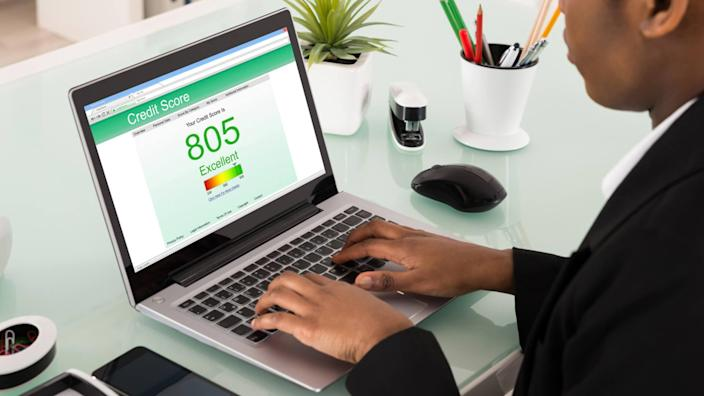 Businesswoman Checking Credit Score On Laptop At Office