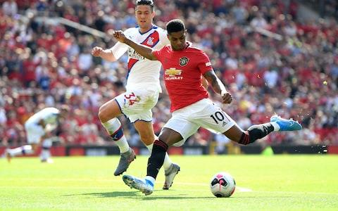 Marcus Rashford shoots as he is closed down by Martin Kelly - Credit: GETTY IMAGES