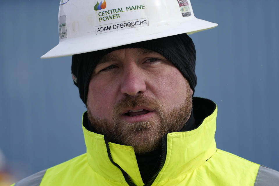 Adam Desrosiers of Central Maine Power speaks to reporters prior to the installation of the first pole of a controversial hydropower transmission corridor, Tuesday, Feb. 9, 2021, near The Forks, Maine. The pole was erected on an existing corridor that had been widened near Moxie Pond. (AP Photo/Robert F. Bukaty)