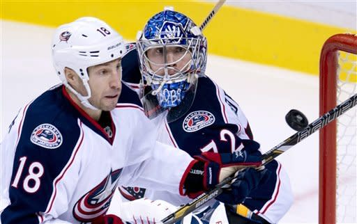 Columbus Blue Jackets' R.J. Umberger (18) stops a shot against the Vancouver Canucks as Blue Jackets goalie Sergei Bobrovsky (72) watches during the second period of an NHL hockey game in Vancouver, British Columbia, Tuesday, March 26, 2013. (AP Photo/The Canadian Press, Jonathan Hayward)
