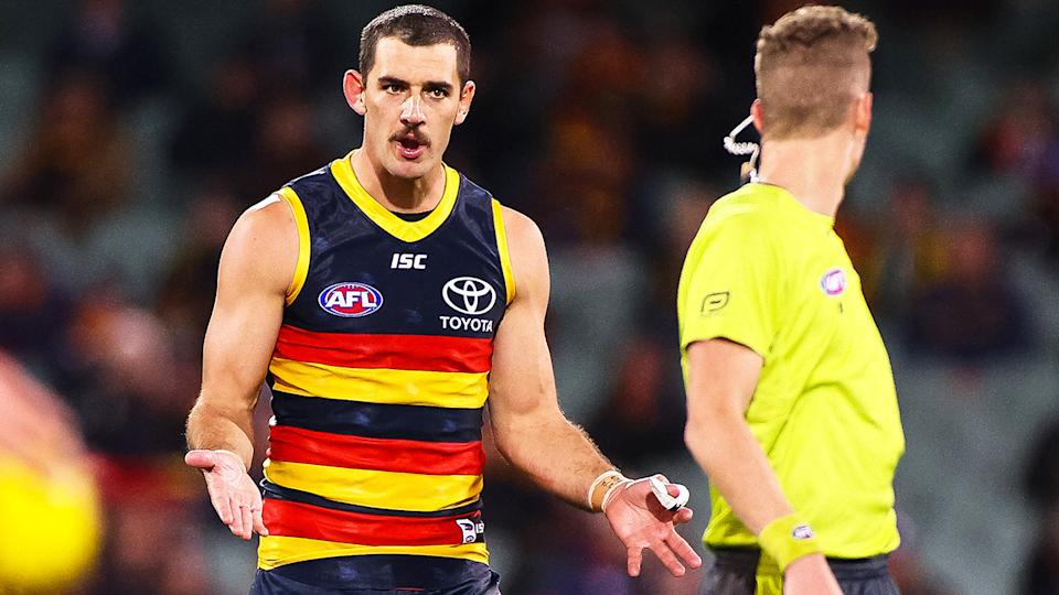 Adelaide Crows forward Taylor Walker is pictured speaking to an umpire.