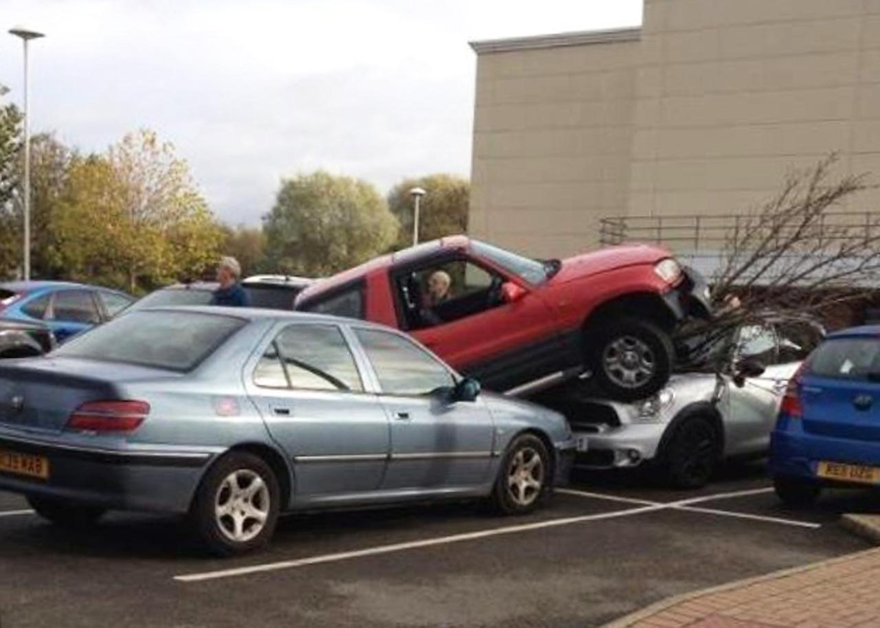 This hapless driver managed to drive over a over a tree, Peugeot 406 and a Mini in an effort to find the best parking spot. The parking blunder was captured on camera by arehouse worker Tom Evans, 27, at a retail park in Rugby, Warks, who said he couldn't believe what he saw. No one was hurt in the mishap - except the driver's ego (SWNS)