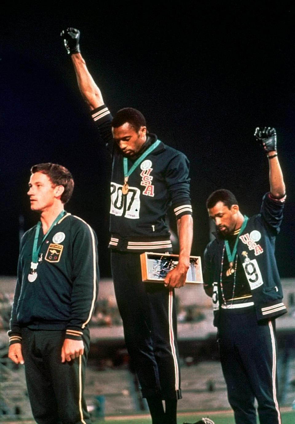 U.S. athletes Tommie Smith, center, and John Carlos extend gloved hands skyward in racial protest during the playing of national anthem at the 1968 Olympics.