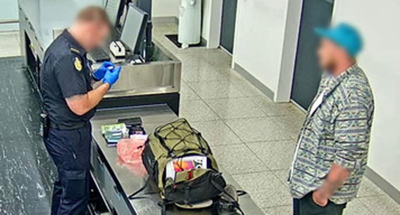 A man speaks with an Australian Border Force officer. A bag sits on a counter between them.