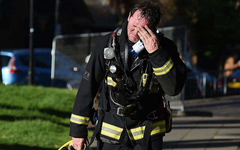 A firemen reacts after battling a huge fire at the Grenfell Towe - Credit: ANDY RAIN/EPA