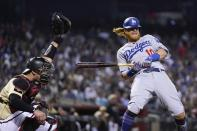 Los Angeles Dodgers' Justin Turner, right, backs away from an inside pitch as Arizona Diamondbacks catcher Carson Kelly reaches up to make the catch during the eighth inning of a baseball game Friday, June 18, 2021, in Phoenix. The Dodgers won 3-0. (AP Photo/Ross D. Franklin)