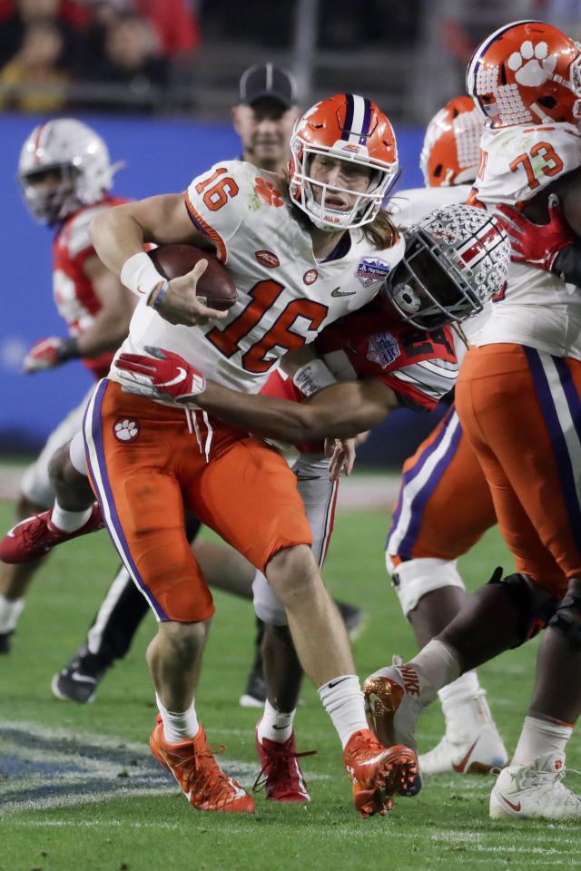 FILE - In this Dec. 28, 2019, file photo, Ohio State cornerback Shaun Wade, right, tackles Clemson quarterback Trevor Lawrence during the first half of the Fiesta Bowl NCAA college football playoff semifinal in Glendale, Ariz. Wade was ejected from the game for targeting. Players ejected from games for targeting will be allowed to remain in the bench area and replay reviews will be limited to two minutes if proposals by the NCAA football rules committee are passed. (AP Photo/Rick Scuteri, File)