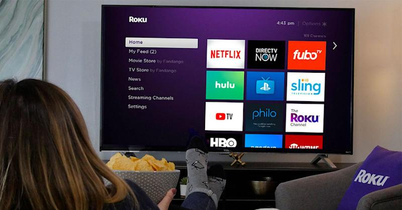 A television displaying the Roku menu and a woman holding a bowl of chips watching from the sofa