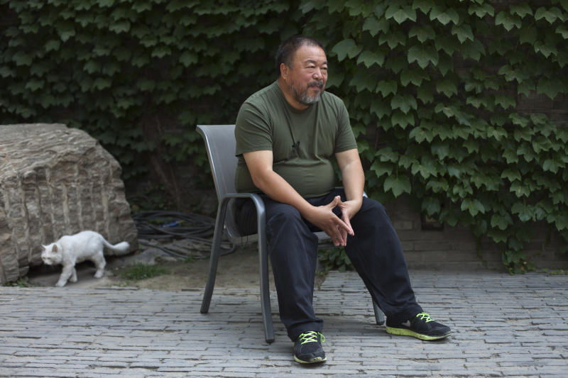 "Artist Ai Weiwei speaks to journalists at the courtyard of his studio in Beijing, China, Wednesday, May 22, 2013. Ai's music video accompanying his heavy metal single ""Dumbass'' released Wednesday depicts an insensitive, overbearing state power that tramples on individual rights. The video is meant to reconstruct his 81-day secret detention in 2011, which was part of the overall crackdown by Chinese authorities on dissent. Ai later was convicted of tax evasion, which his supporters saw as punishment for his activism. (AP Photo/Alexander F. Yuan)"