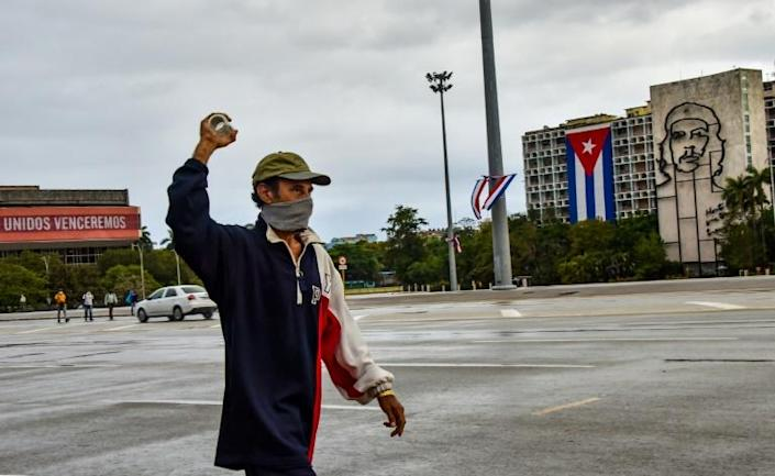 """A man walks in front of the Interior Ministry building with the image of legendary guerrilla leader Ernesto """"Che"""" Guevara at Havana's Revolution square, on May 1, 2020 (AFP Photo/ADALBERTO ROQUE)"""
