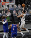 San Antonio Spurs forward Trey Lyles (41) scores over New York Knicks center Nerlens Noel (3) and forward Obi Toppin (1) during the second half of an NBA basketball game in San Antonio, Tuesday, March 2, 2021. (AP Photo/Eric Gay)
