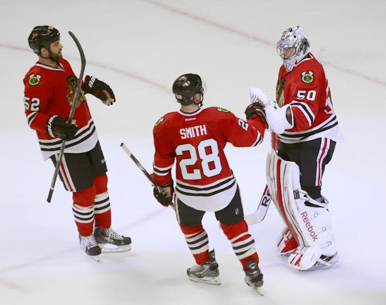 Chicago Blackhawks goalie Corey Crawford (50) celebrates with Brandon Bollig (52) and Ben Smith after the Blackhawks' 2-0 win over the St. Louis Blues in Game 3 of a first-round NHL hockey Stanley Cup playoff series game Monday, April 21, 2014, in Chicago. (AP Photo/Charles Rex Arbogast)