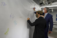 Actor Lin-Manuel Miranda, left, and New York Mayor Bill de Blasio, sign the autograph wall after they toured the grand opening of a Broadway COVID-19 vaccination site intended to jump-start the city's entertainment industry, in New York, Monday, April 12, 2021. (AP Photo/Richard Drew, Pool)