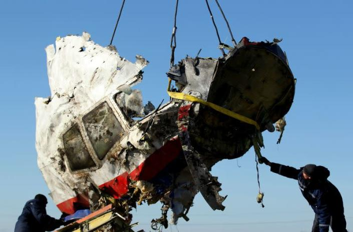 FILE PHOTO: Local workers transport a piece of the Malaysia Airlines flight MH17 wreckage at the site of the plane crash near the village of Hrabove (Grabovo) in Donetsk region