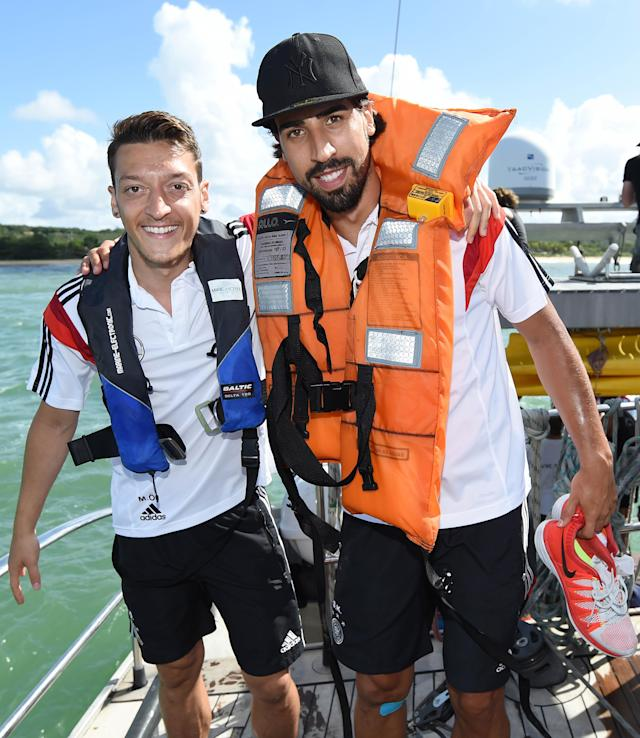 German national soccer player Mset Ozil, left, and Sami Khedira pose on a boat in Santo Andre near Porto Seguro, Brazil, Tuesday, June 10, 2014. The German team got some motivation help from explorer and adventurer Mike Horn during a sailing outing near their camp on Brazil's Atlantic coast. (AP Photo/Markus Gilliar, pool)