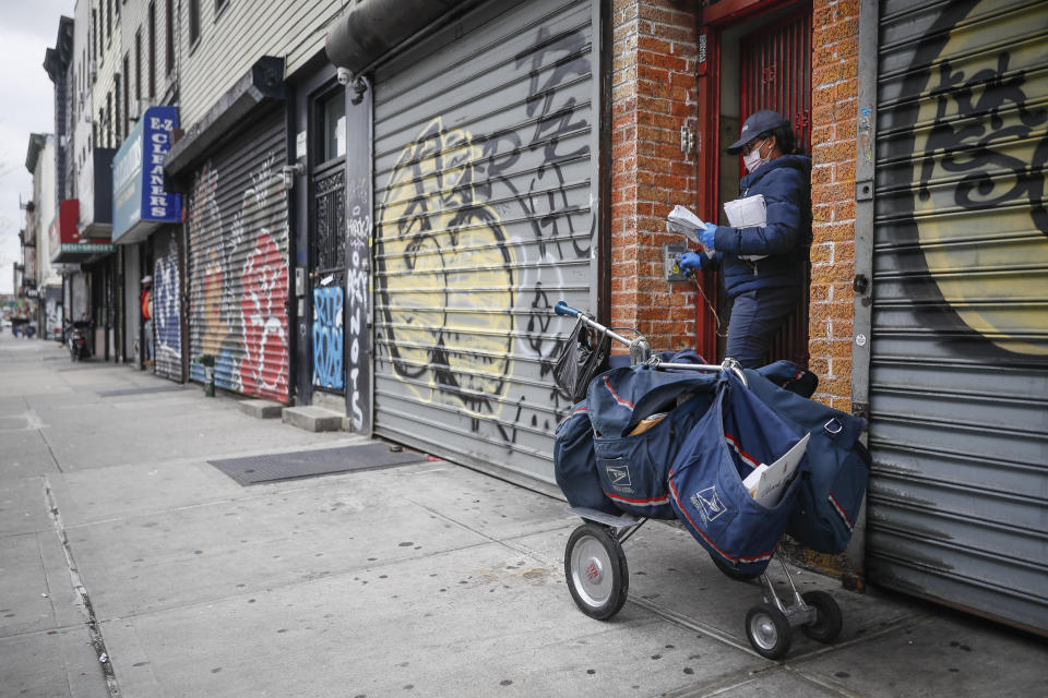 A postal worker delivers mail alongside shuttered storefronts as businesses remain closed due to social distancing protocols, Monday, April 27, 2020, in the Brooklyn borough of New York. (AP Photo/John Minchillo)