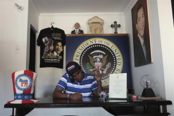Colombian attorney Silvio Carrasquilla takes a phone call while surrounded by his President Obama memorabilia collection which he has used to adorn his home in Turbaco, near Cartagena, Colombia, April 11, 2012.