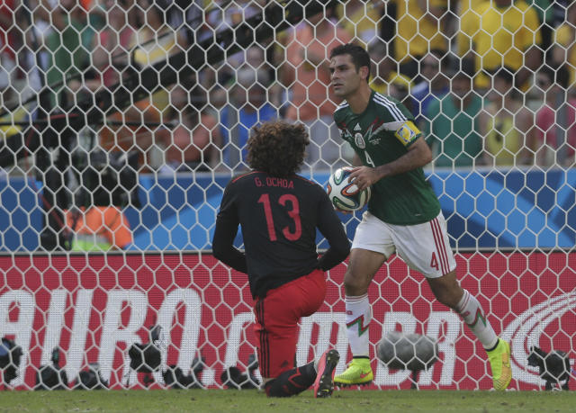 FILE - In this June 29, 2014 file photo, Mexico's Rafael Marquez takes the ball from the net while Mexico's goalkeeper Guillermo Ochoa looks on after the Netherlands scored a penalty during the World Cup round of 16 soccer match between the Netherlands and Mexico at the Arena Castelao in Fortaleza, Brazil. Before playing in Brazil 2014, Marquez said that it was going to be his last World Cup because he would need a cane to play in Russia 2018. Four years later, Mexico's eternal captain is back, a little bit slower on the field, but ready to make history by playing in his fifth World Cup despite his legal troubles. (AP Photo/Marcio Jose Sanchez, File)