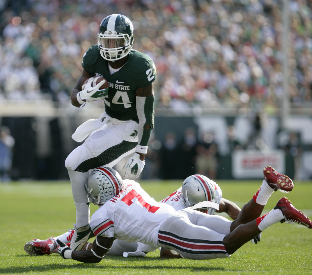 Michigan State's Le'Veon Bell, top, escapes from Ohio State's Travis Howard (7) and Etienne Sabino during the first quarter of an NCAA college football game, Saturday, Sept. 29, 2012, in East Lansing, Mich. (AP Photo/Al Goldis)