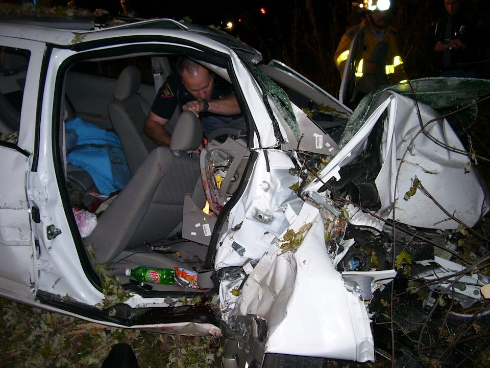 In this 2006 photo, police investigate the wreckage of a 2005 Chevrolet Cobalt that crashed in Wisconsin, killing two teenagers and injuring another. (AP Photo/St. Croix County Sheriff's Office)