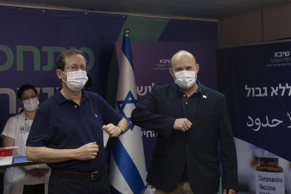 Israeli President Isaac Herzog left, bumps elbows with Prime Minister Naftali Bennett after he received a third coronavirus vaccine injection at Sheba Medical Center in Ramat Gan, Israel, Friday, July 30, 2021. (AP Photo/Maya Alleruzzo, Pool)