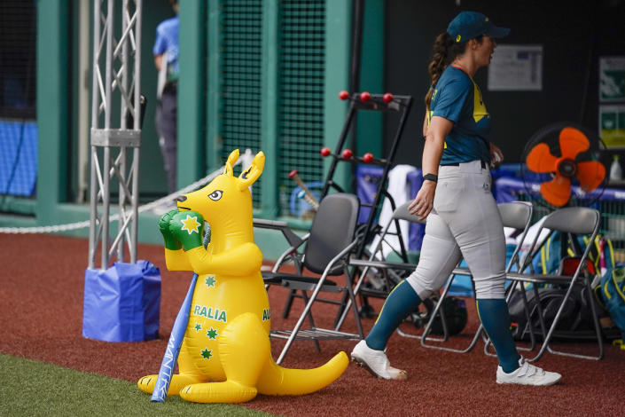 Australia's Kaia Parnaby walks past the team mascot, a boxing kangaroo, to the team dug out during the softball game between the Italy and Australia at the 2020 Summer Olympics, Thursday, July 22, 2021, in Fukushima , Japan. (AP Photo/Jae C. Hong)