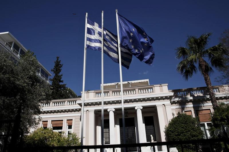 A Greek national flag and an EU flag flutter outside the Maximos mansion