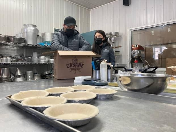 Frédéric Tremblay-Carle, left, packs a meal box at Érablière J.B. Caron in Gracefield, Que., on Feb. 20, 2021. Tremblay-Carle's says it makes more sense to take part in the program than to open right now.