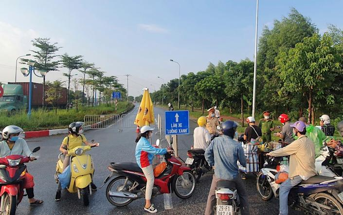 People are turned away at a checkpoint at an entrance to Hanoi - AP
