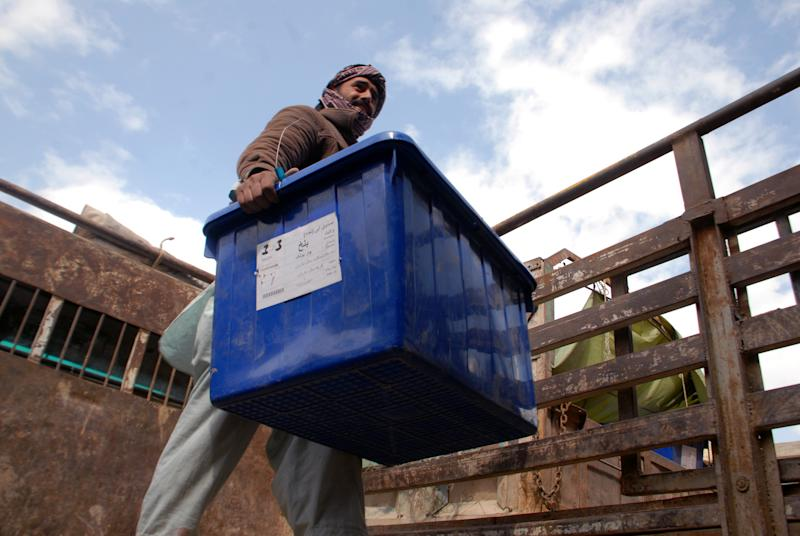 An Afghan election worker carries out of a ballot box from a truck at a warehouse of the Independent Elections Commission in Mazar-i-Sharif, capital of the Balkh province, Afghanistan, Sunday, April 6, 2014. Trucks and donkeys loaded with ballot boxes made their way to counting centers on Sunday as Afghans and the international community sighed with relief that national elections were held without major violence despite a Taliban threat. (AP Photo/Mustafa Najafizada)