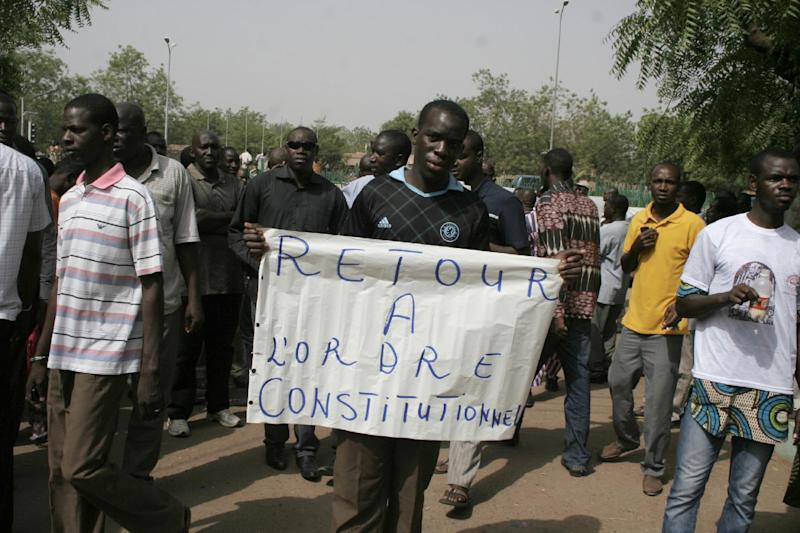 A man carries a sign reading 'Return to constitutional order,' as people gather in protest against the recent military coup, in Bamako, Mali Monday, March 26, 2012. About a thousand demonstrators protested Monday in Mali's capital to demand a return to constitutional order days after mutinous soldiers claimed power in a coup.(AP Photo/Harouna Traore)