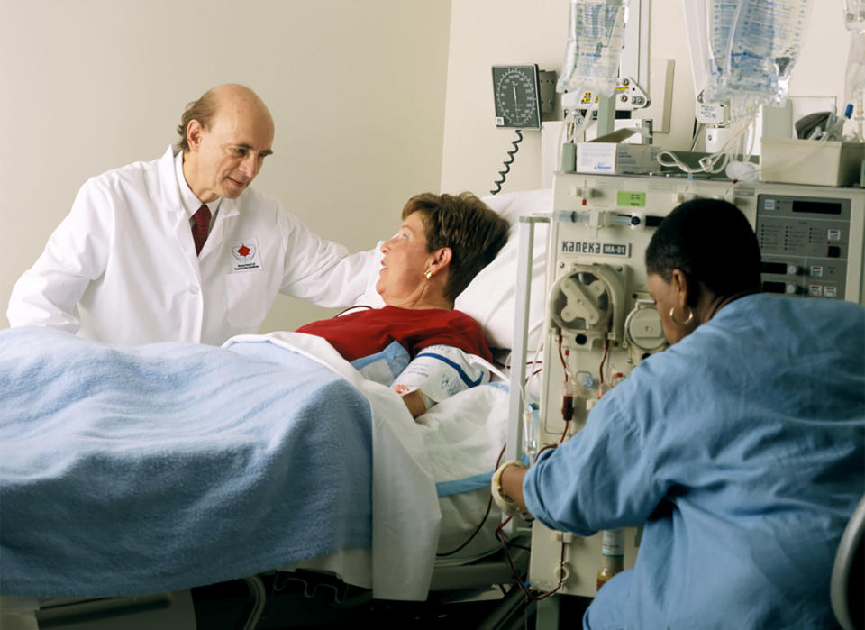 In this undated photo provided by the National Institutes of Health, Harvey J. Alter, left, talks to a patient hooked up to a Kaneka-fuchi Co. Liposorber MA-01, at the National Institutes of Health in Bethesda, Md. Alter and fellow American Charles M. Rice and British-born scientist Michael Houghton jointly won the Nobel Prize for medicine on Monday, Oct. 5, 2020, for their discovery of the hepatitis C virus, a major source of liver disease that affects millions worldwide. (Rhoda Baer/Office of National Institutes of Health History and Stetten Museum via AP)
