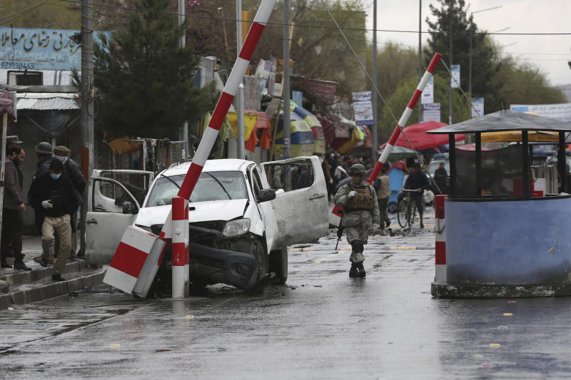 An Afghan security forces member looks at a damaged vehicle after an bomb explosion in Kabul, Afghanistan, Monday, March 30, 2020.  A sticky bomb attached to the vehicle detonated, according to Firdaus Faramraz, spokesman for the Kabul police chief. (AP Photo/Rahmat Gul)