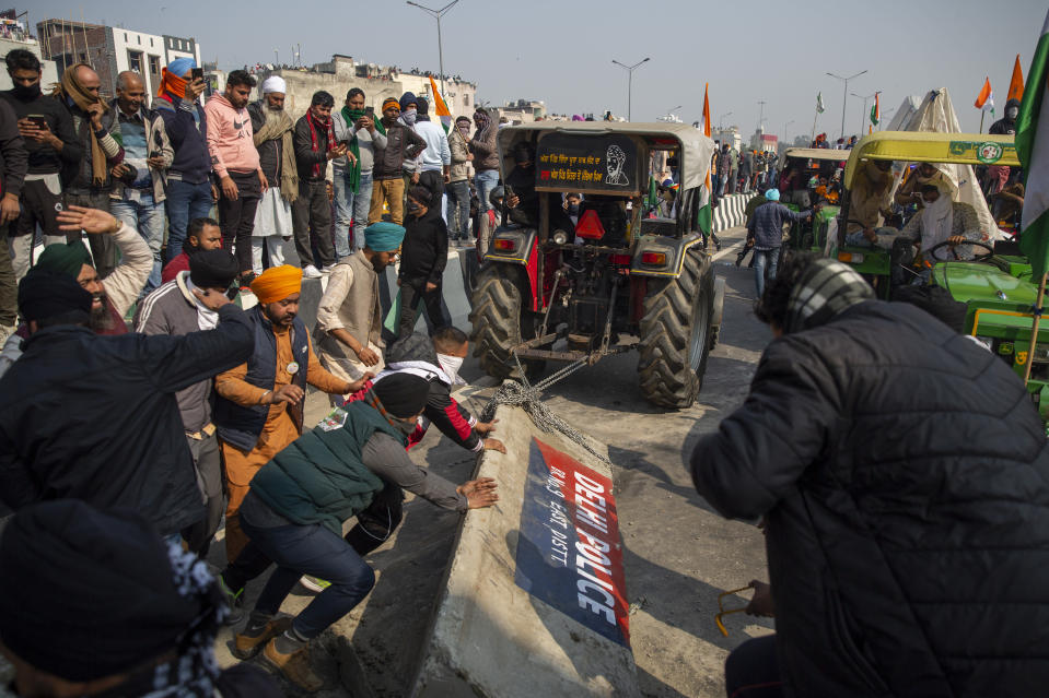 Protesting farmers remove police barricades as they march to the capital during India's Republic Day celebrations in New Delhi, India, Tuesday, Jan. 26, 2021. Tens of thousands of farmers drove a convoy of tractors into the Indian capital as the nation celebrated Republic Day on Tuesday in the backdrop of agricultural protests that have grown into a rebellion and rattled the government. (AP Photo/Altaf Qadri)