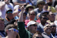 """A fan holds his face mask as he sings """"Back Home Again In Indiana"""" before the Indianapolis 500 auto race at Indianapolis Motor Speedway, Sunday, May 30, 2021, in Indianapolis. (AP Photo/Darron Cummings)"""