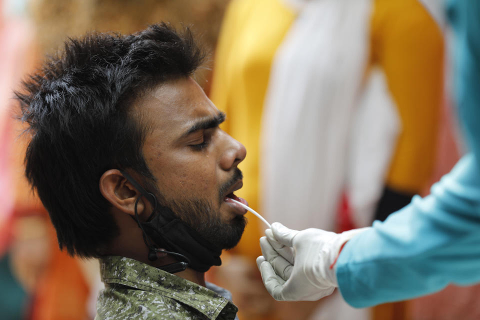 A health worker takes a swab sample to test for COVID-19 in Prayagraj, India, Saturday, April 17, 2021. The global death toll from the coronavirus topped a staggering 3 million people Saturday amid repeated setbacks in the worldwide vaccination campaign and a deepening crisis in places such as Brazil, India and France. (AP Photo/Rajesh Kumar Singh)