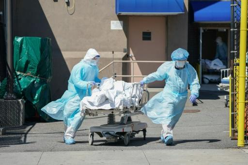Bodies are moved to a refrigeration truck serving as a temporary morgue in New York, the main focus of the US outbreak, with more than 4,750 deaths