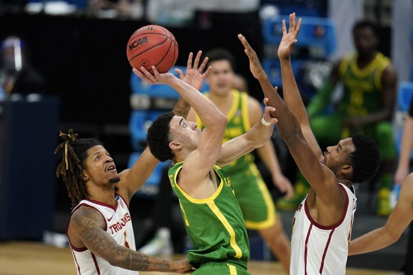 Oregon guard Chris Duarte, center, shoots between Southern California guard Isaiah White, left, and forward Evan Mobley, right, during the second half of a Sweet 16 game in the NCAA men's college basketball tournament at Bankers Life Fieldhouse, Sunday, March 28, 2021, in Indianapolis. (AP Photo/Jeff Roberson)