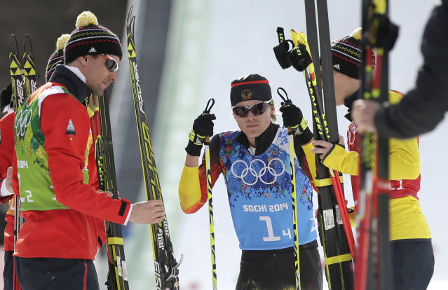 Germany's Fabian Riessle, center, catches his breath after the German team won the silver after the cross-country portion of the Nordic combined Gundersen large hill team competition at the 2014 Winter Olympics, Thursday, Feb. 20, 2014, in Krasnaya Polyana, Russia. (AP Photo/Matthias Schrader)