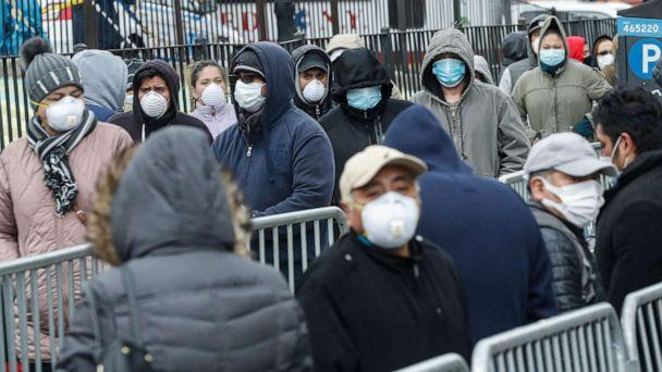 PHOTO: Patients wear personal protective equipment while maintaining social distancing as they wait in line for a COVID-19 test at Elmhurst Hospital Center, March 25, 2020, in New York. (John Minchillo/AP)